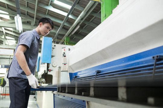 Man controlling hydraulic press machine for cutting steel.