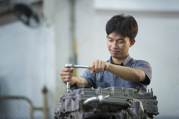 Man are repairing car engine at garage.