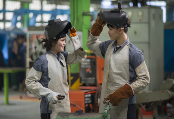 Man and woman welding in factory.industrial worker.