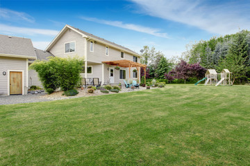 Beautiful house backyard with well kept lawn and patio area