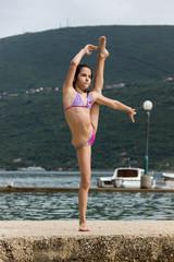 Юная девочка танцует и занимается акробатикой на побережье. Черногория, 2016