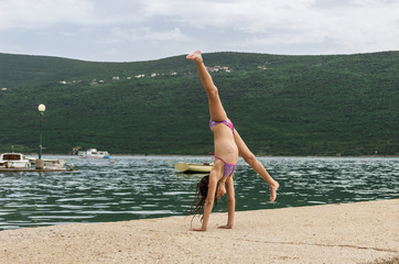 Young girl dancing, acrobatics on the pier.