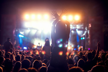 Girl on shoulders in the crowd at a music festival.