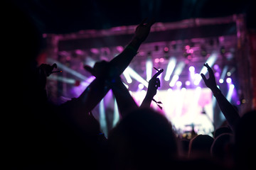 Photo of a crowd, happy people enjoying rock concert, raised up hands and clapping of pleasure, active night life concept.