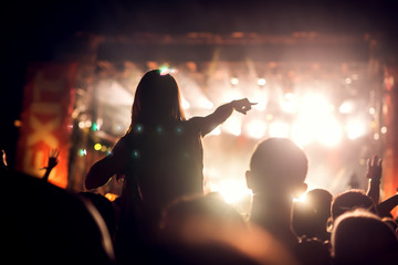 Girl on shoulders in the crowd at a music festival. Blurred movement.