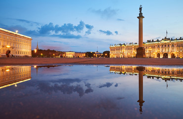Russia, Saint-Petersburg, 03 July 2016: Palace Square with night illumination, Winter Palace, Hermitage, Alexander Column, reflection in a water pool after a rain, a lot tourists, sunset, water mirror