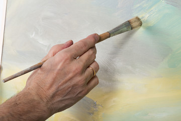 An artist hand painting in studio. Selective focus