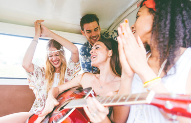 Hippie friends having fun into a vintage van, playing the guitar