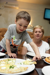 Grandmother and grandson eating pizza