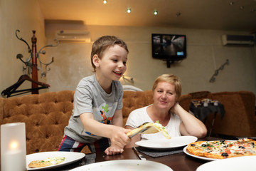 Grandmother with grandson eating pizza