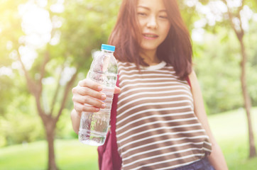 Close up female hand holding water while smiling at summer green park outdoor and bokeh nature background, healthy concept.