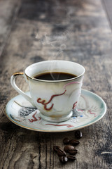 Coffee cup vintage style and beans coffee on a rustic wooden table