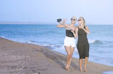 Blonde female Friends Taking Self Portrait and filming on the beach