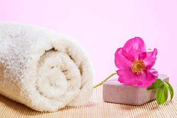 Cotton towel, soap bar and fresh wild rose flower bud