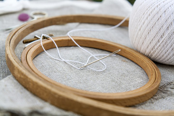 Set for embroidery, garment needle and embroidery hoop on unbleached linen fabric. Selective focus, shallow depth of field