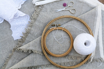 Set for embroidery, garment needle, thread, scissors and embroidery hoop on unbleached linen fabric. Top view