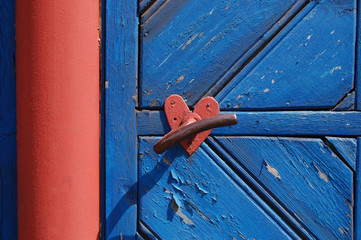 Door handle with heart shape ornament in red on blue background