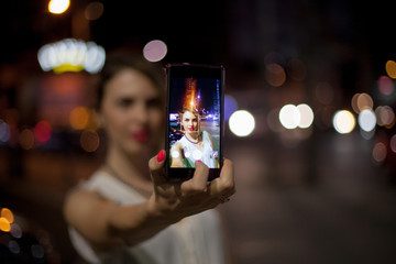 Young woman taking selfie in the city