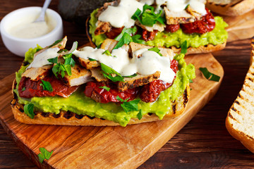 Avocado Sandwich with sunshine dried tomatoes, roasted pork and sauce herbs