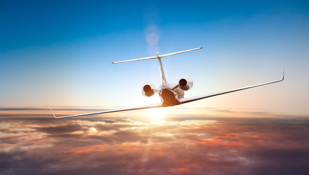 Private jet plane flying above clouds