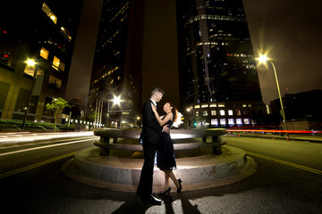 Los Angeles nightlife with an interracial dating couple on a busy downtown street at night.