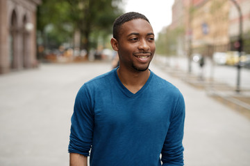 Young black man in city walking happy face