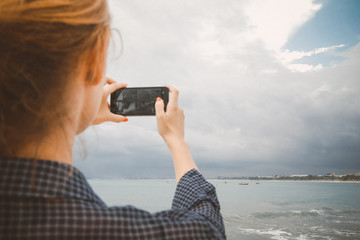 Woman taking photos of the beach with cell phone during the cloudy day