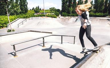 Skateboarding woman practicing at skatepark