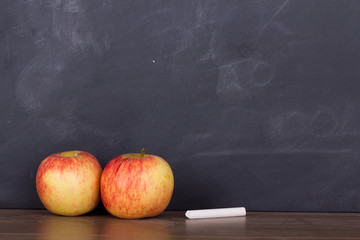 Apple on a wooden surface against a blackboard