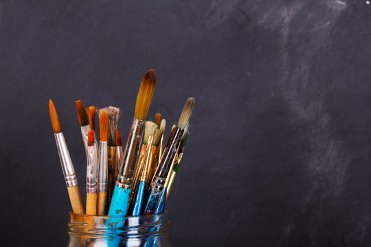 Paint brushes in a pot against a black background