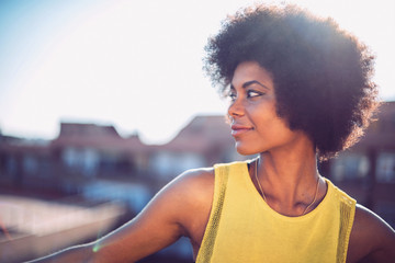Beautiful African girl with curly hair on the rooftop