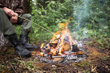A man warms himself by the fire in the forest, rain, autumn