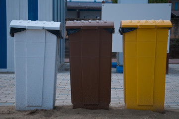 garbage cans in white, brown and yellow