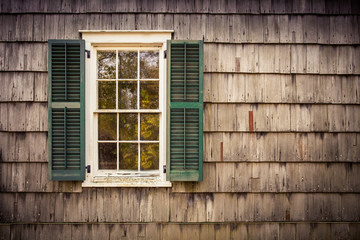 Exterior window with shutters on cedar shake shingled home