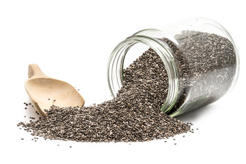Chia seeds in an overturned glass jar with a wooden spoon next to it seen from front on white background