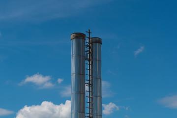 Edelstahl Industrie Schornsteine vor blauem Himmel
