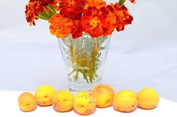 Букет бархатцев и абрикосы на переднем плане