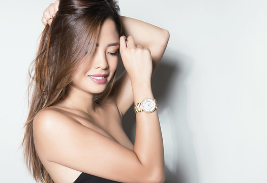 beautiful young asian woman with long hair posing with wrist watch