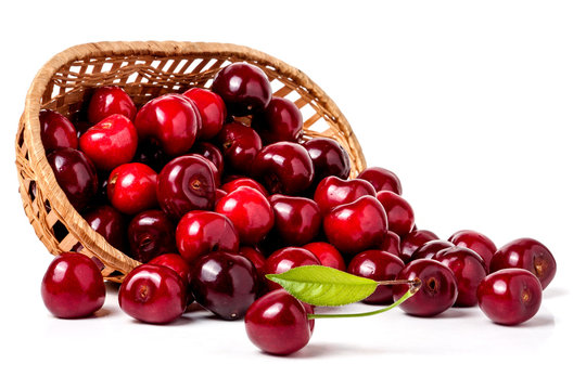 cherries in a wicker basket isolated on white background