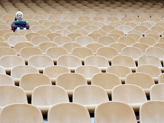 many chairs and a lone girl on stadium