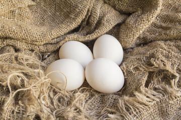 Closeup of a fresh white eggs on canvas Brown