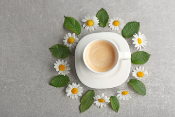 Cup of coffee with fresh flowers lying around on color background