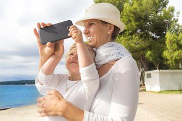 Mutter und Tochter im Urlaub am Meer machen ein Foto mit dem Smartphone