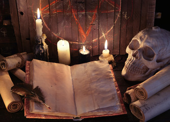 Open witch book with paper scrolls and evil candles against pentagram background