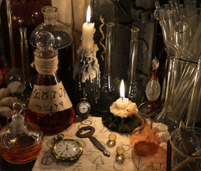 Close up with clock, key, candle, bottles and magic objects