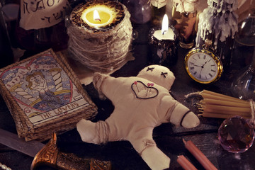 Close up of woodoo doll, knife, burning candles and magic objects