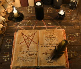 Black candles and open magic book with pentagram