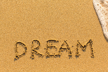 Dream - drawn by hand on a sandy golden sea beach.