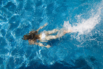 girl in a white bathing suit under the water in the pool
