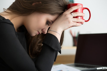 Tired female employee at workplace in office touching her head